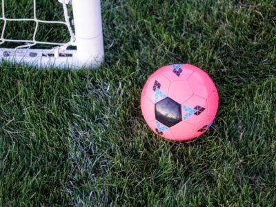 A pink football next to the corner of a goal post