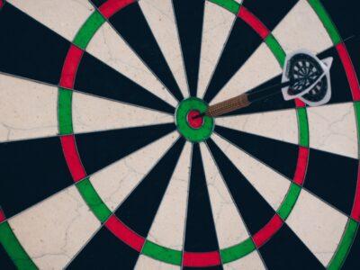 A darts board with an arrow in the bullseye