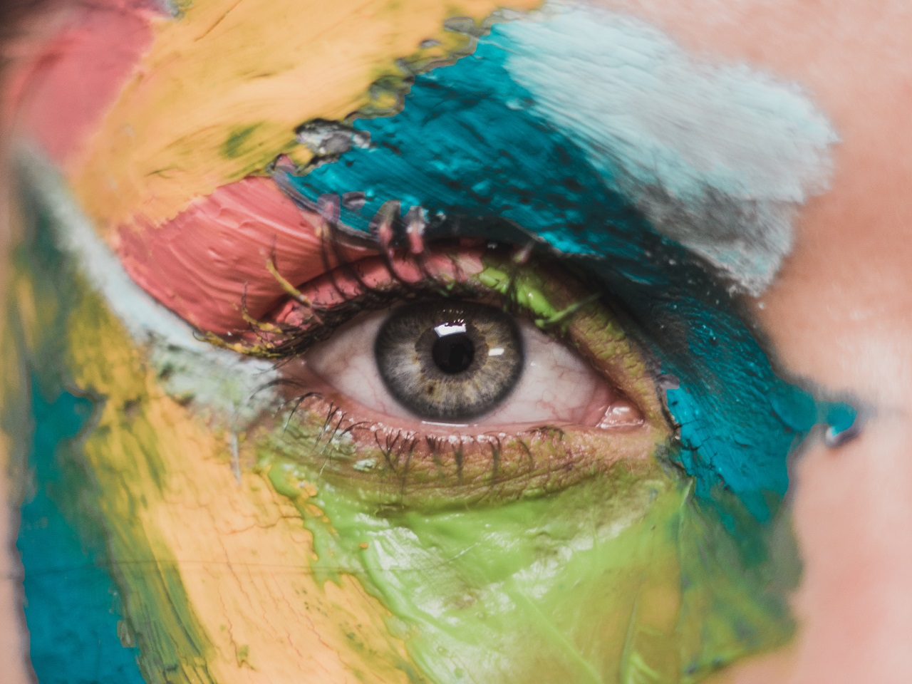 Close up of a human eye with multicoloured paint around their eye. Image by Daniel Apodaca on Unsplash